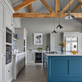 Inspiration for an expansive transitional l-shaped open plan kitchen in Other with an integrated sink, shaker cabinets, grey cabinets, quartzite benchtops, blue splashback, stone tile splashback, stainless steel appliances, porcelain floors, with island, grey floor and white benchtop.