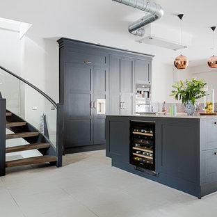 ロンドンの大きいインダストリアルスタイルのおしゃれなキッチン (エプロンフロントシンク、シェーカースタイル扉のキャビネット、青いキャビネット、珪岩カウンター、マルチカラーのキッチンパネル、モザイクタイルのキッチンパネル、黒い調理設備、コンクリートの床、グレーの床) の写真