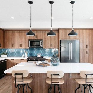 Idéer för funkis l-kök, med en undermonterad diskho, släta luckor, skåp i mellenmörkt trä, blått stänkskydd, rostfria vitvaror, mellanmörkt trägolv, en köksö och brunt golv
