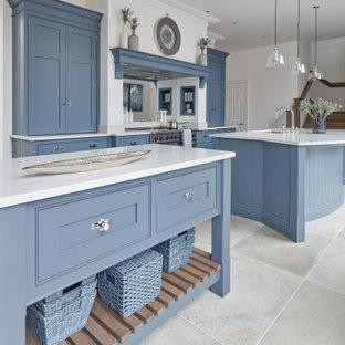 Große Klassische Wohnküche in L-Form mit Unterbauwaschbecken, Schrankfronten im Shaker-Stil, blauen Schränken, Quarzwerkstein-Arbeitsplatte, Küchenrückwand in Weiß, Rückwand aus Spiegelfliesen, Küchengeräten aus Edelstahl, Kalkstein, zwei Kücheninseln, beigem Boden und weißer Arbeitsplatte in Gloucestershire