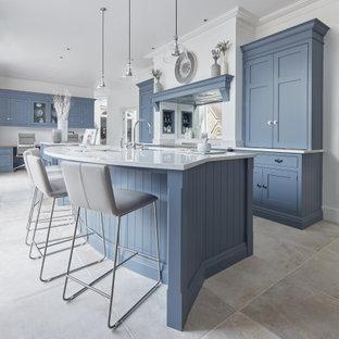 Bild på ett stort vintage vit vitt l-kök, med en undermonterad diskho, skåp i shakerstil, blå skåp, bänkskiva i kvarts, vitt stänkskydd, spegel som stänkskydd, rostfria vitvaror, kalkstensgolv, flera köksöar och beiget golv