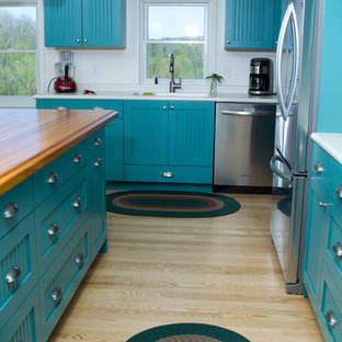 Design ideas for a large arts and crafts galley eat-in kitchen in Minneapolis with an integrated sink, shaker cabinets, blue cabinets, wood benchtops, white splashback, stainless steel appliances, light hardwood floors and with island.