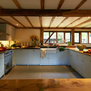 Design ideas for a medium sized farmhouse u-shaped kitchen/diner in Other with a breakfast bar, shaker cabinets, blue cabinets, granite worktops, beige splashback, coloured appliances and a belfast sink.