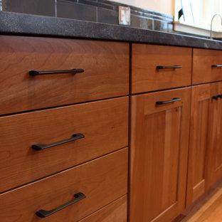 他の地域の中くらいのインダストリアルスタイルのおしゃれなキッチン (ダブルシンク、シェーカースタイル扉のキャビネット、中間色木目調キャビネット、御影石カウンター、グレーのキッチンパネル、セラミックタイルのキッチンパネル、シルバーの調理設備、無垢フローリング、アイランドなし、茶色い床) の写真