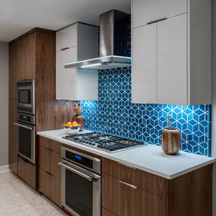 This is an example of a mid-sized midcentury l-shaped eat-in kitchen in Austin with medium wood cabinets, blue splashback, ceramic splashback, stainless steel appliances, with island, beige floor and grey benchtop.