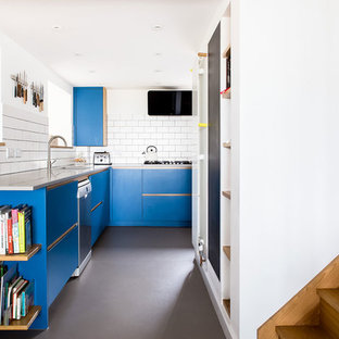 Design ideas for a medium sized scandinavian l-shaped open plan kitchen in Wiltshire with a submerged sink, flat-panel cabinets, blue cabinets, white splashback, stainless steel appliances, concrete flooring, no island, metro tiled splashback and grey floors.
