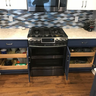 Mid-sized transitional enclosed kitchen ideas - Example of a mid-sized transitional u-shaped laminate floor and brown floor enclosed kitchen design in Detroit with an undermount sink, recessed-panel cabinets, blue cabinets, quartzite countertops, multicolored backsplash, glass tile backsplash, black appliances, an island and white countertops