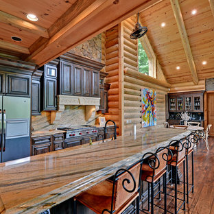 Example of a classic galley open concept kitchen design in Atlanta with stone slab backsplash, raised-panel cabinets, dark wood cabinets, beige backsplash and stainless steel appliances