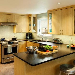 На фото: п-образные кухни среднего размера в стиле ретро с обеденным столом, врезной раковиной, светлыми деревянными фасадами, синим фартуком, фартуком из плитки кабанчик, техникой из нержавеющей стали, полуостровом и пробковым полом