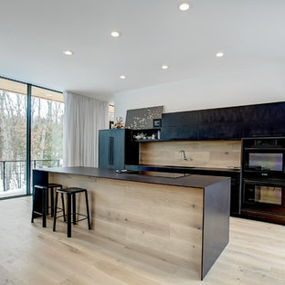Inspiration for a mid-sized modern galley open plan kitchen in Grand Rapids with an integrated sink, flat-panel cabinets, black cabinets, quartz benchtops, timber splashback, black appliances, light hardwood floors, with island and beige floor.