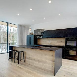 グランドラピッズの中くらいのモダンスタイルのおしゃれなキッチン (一体型シンク、フラットパネル扉のキャビネット、黒いキャビネット、クオーツストーンカウンター、木材のキッチンパネル、黒い調理設備、淡色無垢フローリング、ベージュの床) の写真