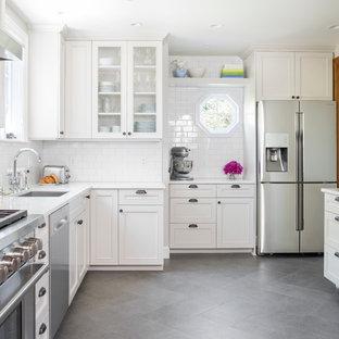 Idéer för mellanstora vintage l-kök, med en undermonterad diskho, vita skåp, bänkskiva i kvarts, vitt stänkskydd, stänkskydd i tunnelbanekakel, rostfria vitvaror, klinkergolv i porslin och luckor med profilerade fronter