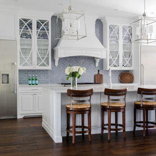 Inspiration för stora maritima vitt l-kök, med luckor med upphöjd panel, vita skåp, grått stänkskydd, mörkt trägolv, en köksö och brunt golv