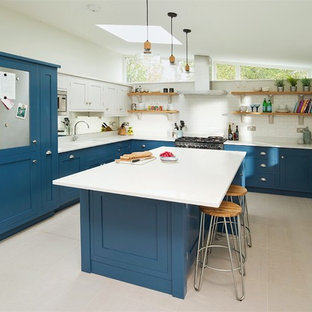 This is an example of a medium sized classic u-shaped kitchen/diner in Hertfordshire with blue cabinets, quartz worktops, stainless steel appliances, an island, recessed-panel cabinets, white splashback, metro tiled splashback and grey floors.