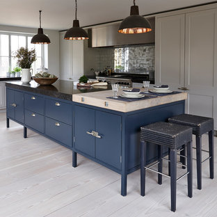 Inspiration for a mid-sized contemporary l-shaped open plan kitchen in London with an integrated sink, flat-panel cabinets, blue cabinets, marble benchtops, metallic splashback, mirror splashback, stainless steel appliances, light hardwood floors, with island, brown floor and black benchtop.