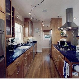 Idéer för mellanstora funkis blått kök, med en nedsänkt diskho, luckor med infälld panel, skåp i mellenmörkt trä, rostfria vitvaror, mellanmörkt trägolv, bänkskiva i kvarts, stänkskydd med metallisk yta och stänkskydd i metallkakel