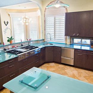 ダラスの大きいエクレクティックスタイルのおしゃれなキッチン (アンダーカウンターシンク、フラットパネル扉のキャビネット、濃色木目調キャビネット、ガラスカウンター、シルバーの調理設備の、トラバーチンの床、ターコイズのキッチンカウンター) の写真