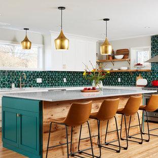 Foto di una grande cucina a L chic con ante bianche, paraspruzzi con piastrelle in ceramica, isola, ante con riquadro incassato, paraspruzzi verde, elettrodomestici in acciaio inossidabile, parquet chiaro, pavimento beige e top grigio