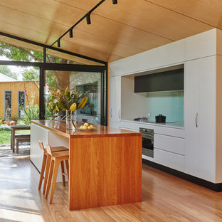 Photo of a contemporary galley kitchen in Melbourne with a double-bowl sink, flat-panel cabinets, white cabinets, wood benchtops, blue splashback, glass sheet splashback, panelled appliances, medium hardwood floors, with island and brown floor.