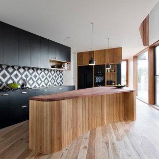 Mittelgroße Moderne Küche mit flächenbündigen Schrankfronten, schwarzen Schränken, Arbeitsplatte aus Holz, bunter Rückwand, Rückwand aus Zementfliesen, schwarzen Elektrogeräten, braunem Holzboden und Kücheninsel in Melbourne