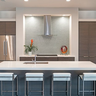 Photo of a large modern eat-in kitchen in Atlanta with an undermount sink, flat-panel cabinets, brown cabinets, grey splashback, glass tile splashback, stainless steel appliances, medium hardwood floors, with island and quartz benchtops.