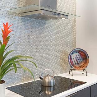 Moderne Wohnküche mit flächenbündigen Schrankfronten, braunen Schränken, Küchenrückwand in Grau, Rückwand aus Glasfliesen, Küchengeräten aus Edelstahl, Unterbauwaschbecken, braunem Holzboden und Kücheninsel in Atlanta