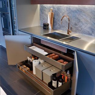 Idee per un'ampia cucina design con ante lisce, ante beige, top in marmo, paraspruzzi beige, paraspruzzi con lastra di vetro, elettrodomestici da incasso, pavimento con piastrelle in ceramica, isola, pavimento nero e top grigio