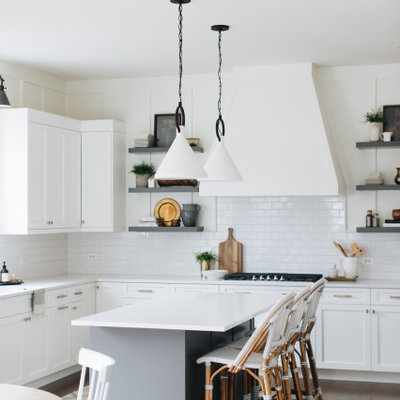 Inspiration for a transitional l-shaped dark wood floor and brown floor eat-in kitchen remodel in Chicago with shaker cabinets, white cabinets, white backsplash, subway tile backsplash, an island and white countertops