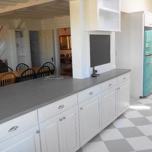 Zweizeilige, Mittelgroße Maritime Küche mit Landhausspüle, profilierten Schrankfronten, weißen Schränken, Quarzwerkstein-Arbeitsplatte, Küchenrückwand in Weiß, Rückwand aus Metrofliesen, bunten Elektrogeräten, gebeiztem Holzboden, Halbinsel und Vorratsschrank in Sonstige