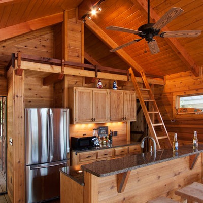 Mid-sized mountain style galley medium tone wood floor open concept kitchen photo in Other with recessed-panel cabinets, stainless steel appliances, light wood cabinets, granite countertops, wood backsplash and an island
