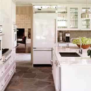 Klassische Küche mit Doppelwaschbecken, Glasfronten, weißen Schränken, Küchenrückwand in Grau, Rückwand aus Metrofliesen, weißen Elektrogeräten und Schieferboden in Dallas