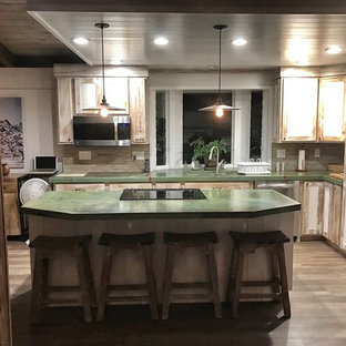 Mid-sized country l-shaped eat-in kitchen in Hawaii with an undermount sink, recessed-panel cabinets, distressed cabinets, concrete benchtops, multi-coloured splashback, glass tile splashback, stainless steel appliances, laminate floors, with island and brown floor.