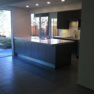 Idee per una cucina moderna di medie dimensioni con lavello sottopiano, ante lisce, ante in acciaio inossidabile, top in quarzite, paraspruzzi bianco, paraspruzzi in lastra di pietra, elettrodomestici in acciaio inossidabile, pavimento in gres porcellanato e 2 o più isole