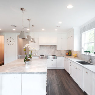 Example of a large transitional u-shaped porcelain tile and brown floor kitchen design in Miami with a drop-in sink, white cabinets, marble countertops, multicolored backsplash, stone slab backsplash, stainless steel appliances, an island, shaker cabinets and gray countertops