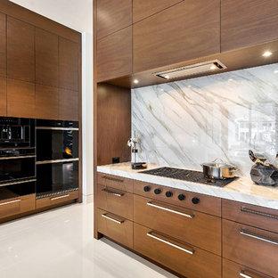 На фото: класса люкс большие кухни в стиле модернизм с накладной раковиной, плоскими фасадами, фасадами цвета дерева среднего тона, столешницей из оникса, бежевым фартуком, мраморным полом, островом, белым полом и бежевой столешницей