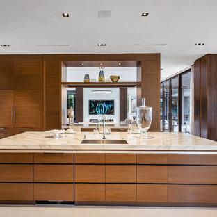 マイアミの大きいモダンスタイルのおしゃれなアイランドキッチン (ドロップインシンク、フラットパネル扉のキャビネット、中間色木目調キャビネット、オニキスカウンター、ベージュキッチンパネル、大理石の床、白い床、ベージュのキッチンカウンター) の写真