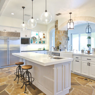 Inspiration for a large classic u-shaped kitchen/diner in Austin with a belfast sink, raised-panel cabinets, white cabinets, glass worktops, white splashback, marble splashback, stainless steel appliances, limestone flooring, an island, brown floors and yellow worktops.