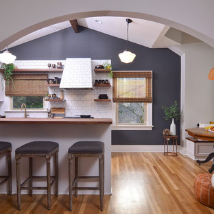 Small transitional eat-in kitchen pictures - Small transitional galley medium tone wood floor and brown floor eat-in kitchen photo in Portland with white cabinets, wood countertops, white backsplash, subway tile backsplash, a peninsula and brown countertops