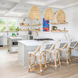 Photo of a beach style kitchen in Charleston with an undermount sink, flat-panel cabinets, grey cabinets, white splashback, subway tile splashback, stainless steel appliances, light hardwood floors, a peninsula, beige floor, white benchtop and coffered.
