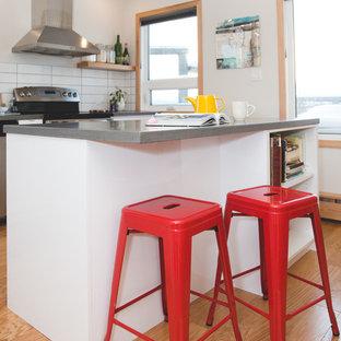 他の地域のトランジショナルスタイルのおしゃれなアイランドキッチン (アンダーカウンターシンク、フラットパネル扉のキャビネット、白いキャビネット、コンクリートカウンター、白いキッチンパネル、セラミックタイルのキッチンパネル、シルバーの調理設備、無垢フローリング) の写真