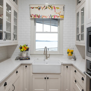 Small beach style u-shaped kitchen in Minneapolis with a farmhouse sink, glass-front cabinets, beige cabinets, white splashback, subway tile splashback, stainless steel appliances, dark hardwood floors, no island and white benchtop.