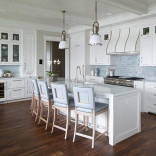 Maritime Küche mit Schrankfronten im Shaker-Stil, weißen Schränken, Küchenrückwand in Blau, Rückwand aus Metrofliesen, Küchengeräten aus Edelstahl, dunklem Holzboden, Kücheninsel, braunem Boden und weißer Arbeitsplatte in Minneapolis