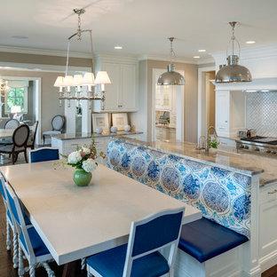 Идея дизайна: огромная п-образная кухня в морском стиле с обеденным столом, фасадами в стиле шейкер, белыми фасадами, бежевым фартуком, техникой из нержавеющей стали, темным паркетным полом, островом, раковиной в стиле кантри, мраморной столешницей, фартуком из плитки мозаики и коричневым полом