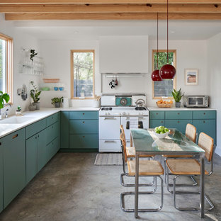 Inspiration for a mid-sized scandinavian l-shaped eat-in kitchen in Austin with an undermount sink, flat-panel cabinets, green cabinets, quartz benchtops, white appliances, concrete floors, no island, grey floor and white benchtop.