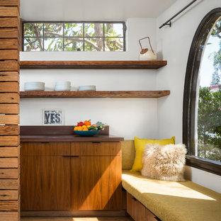 ロサンゼルスの小さいコンテンポラリースタイルのおしゃれなキッチン (フラットパネル扉のキャビネット、濃色木目調キャビネット、アンダーカウンターシンク、木材カウンター、茶色いキッチンパネル、木材のキッチンパネル、パネルと同色の調理設備、無垢フローリング、アイランドなし、茶色い床) の写真