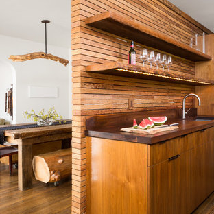 ロサンゼルスの小さいコンテンポラリースタイルのおしゃれなキッチン (アンダーカウンターシンク、フラットパネル扉のキャビネット、濃色木目調キャビネット、木材カウンター、パネルと同色の調理設備、茶色いキッチンパネル、木材のキッチンパネル、無垢フローリング、アイランドなし、茶色い床) の写真
