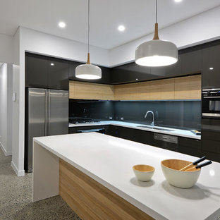 Inspiration for a contemporary l-shaped kitchen in Sunshine Coast with a double-bowl sink, flat-panel cabinets, black cabinets, black splashback, glass sheet splashback, black appliances, concrete floors, with island, grey floor and white benchtop.