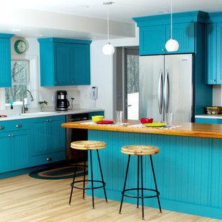ミルウォーキーの中くらいのエクレクティックスタイルのおしゃれなキッチン (一体型シンク、ターコイズのキャビネット、木材カウンター、白いキッチンパネル、シルバーの調理設備、淡色無垢フローリング、フラットパネル扉のキャビネット、茶色い床、白いキッチンカウンター) の写真