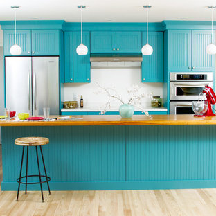 Inspiration for a mid-sized eclectic l-shaped light wood floor eat-in kitchen remodel in Milwaukee with blue cabinets, wood countertops, white backsplash, stainless steel appliances and an island
