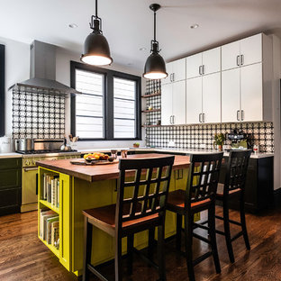 Mid-sized eclectic enclosed kitchen photos - Inspiration for a mid-sized eclectic u-shaped dark wood floor and brown floor enclosed kitchen remodel in San Francisco with black cabinets, multicolored backsplash, stainless steel appliances, an island, white countertops, an undermount sink, recessed-panel cabinets, solid surface countertops and ceramic backsplash